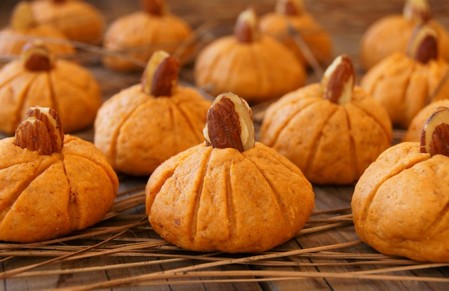 Several Pumpkin Almond Cookies on wood surface.