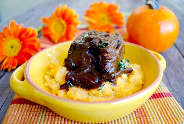 Pumpkin Braised Short Ribs in a yellow bowl with orange daisies behind it.
