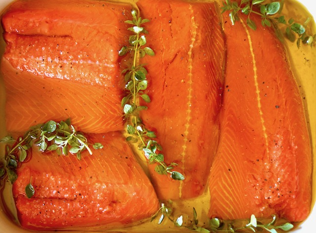 salmon fillets in baking pan with thyme and olive oil