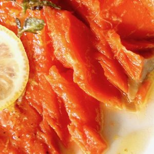 Fillet of oil poached salmon flaked apart with lemon