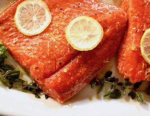One fillet of Olive Oil Poached Fish (Salmon) on a white platter with lemon
