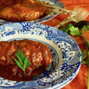 Chicken with brown-red sauce on a blue and white plate