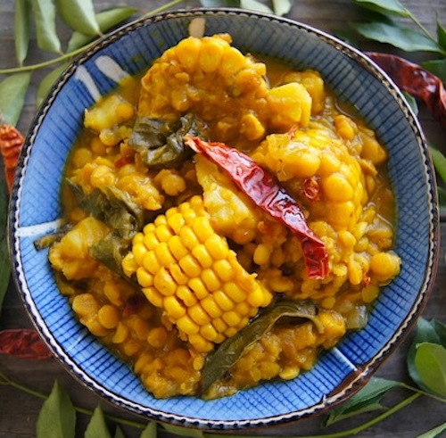 What is a comfort food? This is one, Curried Corn Stew with Lentils and Sweet Potato in pretty boue bowl surrounded with fresh bay leaves