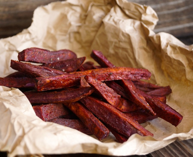 Chile-Lemon Roasted Purple Sweet Potato Fries on beige, crumpled parchment.