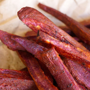 Chile Lemon Roasted Purple Sweet Potato Fries on parchment paper