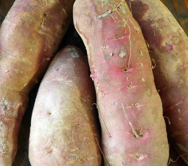 four raw slightly dirty purple sweet potatoes