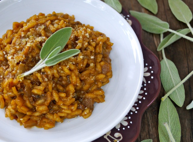 Fall Pumpkin Risotto in a white bowl with fresh sage leaves.