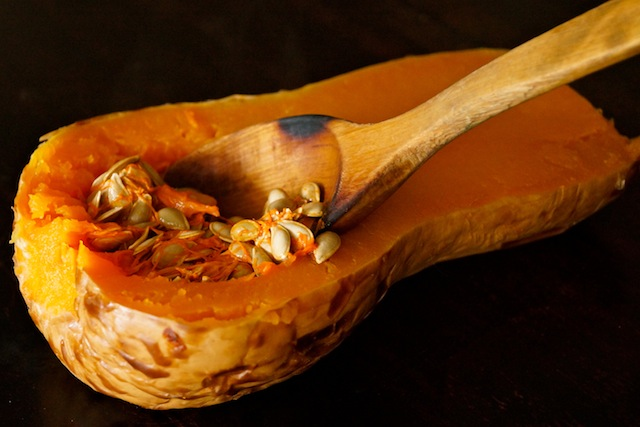 half of a roasted butternut squash with wooden spoon removing seeds