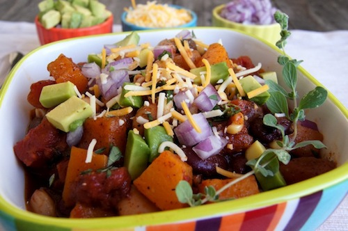 What is a comfort food? This is one, Roasted Butternut Squash Vegan Chili in colorful striped bowl with fresh oregano sprig