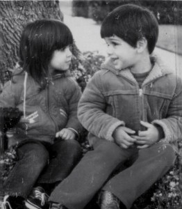 Valentina and her brother John as little kids sitting by a tree trunk.