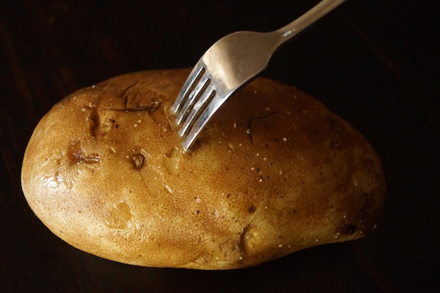 Russet potato with fork in it