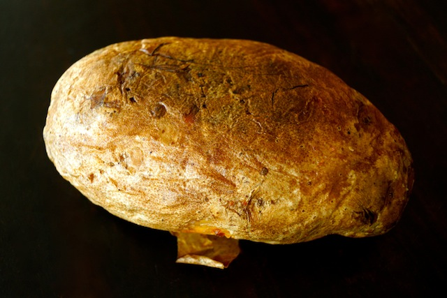 While Russet baked potato on black background