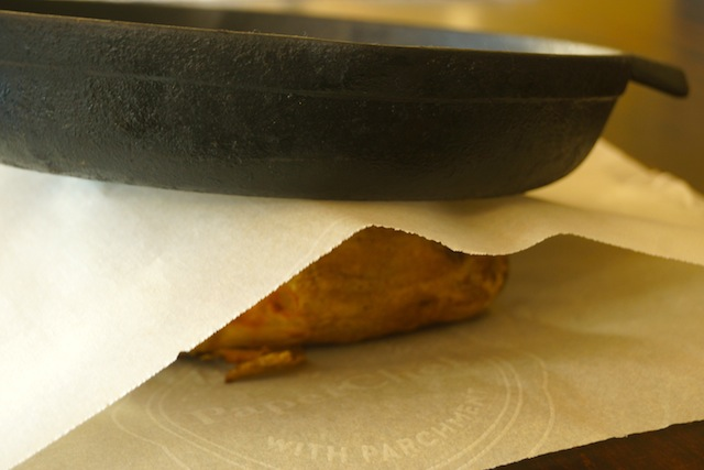 Russet potato between pieces of parchment with pan on top