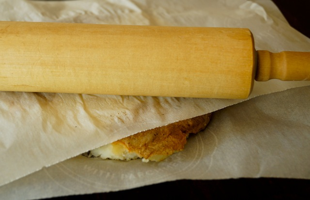 Rolling pin on top of parchment paper with Russet potato under it