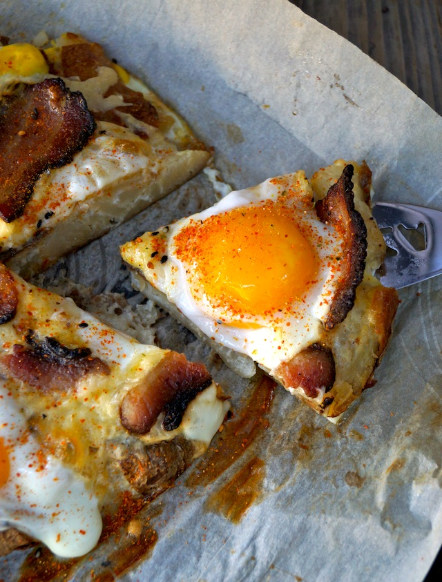 One slice of Smashed Potato Egg Pizza with Bacon being held up
