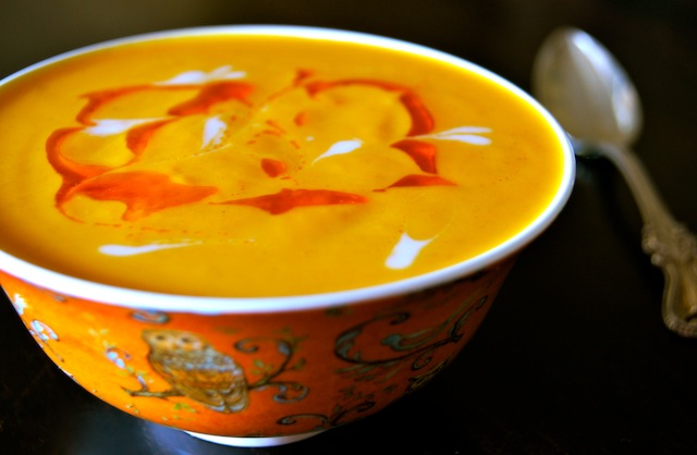 What is a comfort food? This is one, Vegan Coconut Spiced Carrot Soup in a pretty orange bowl with swirled oil on top