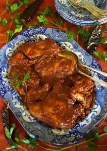 Really good chicken recipe with brown-red sauce on big blue and white platter with parsely