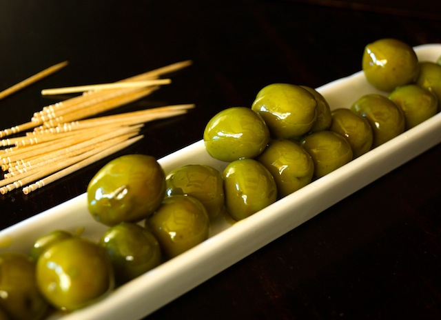 Warm Castelvetrano Olives in a long, diagonal olive dish, with a pile of toothpicks next to it.