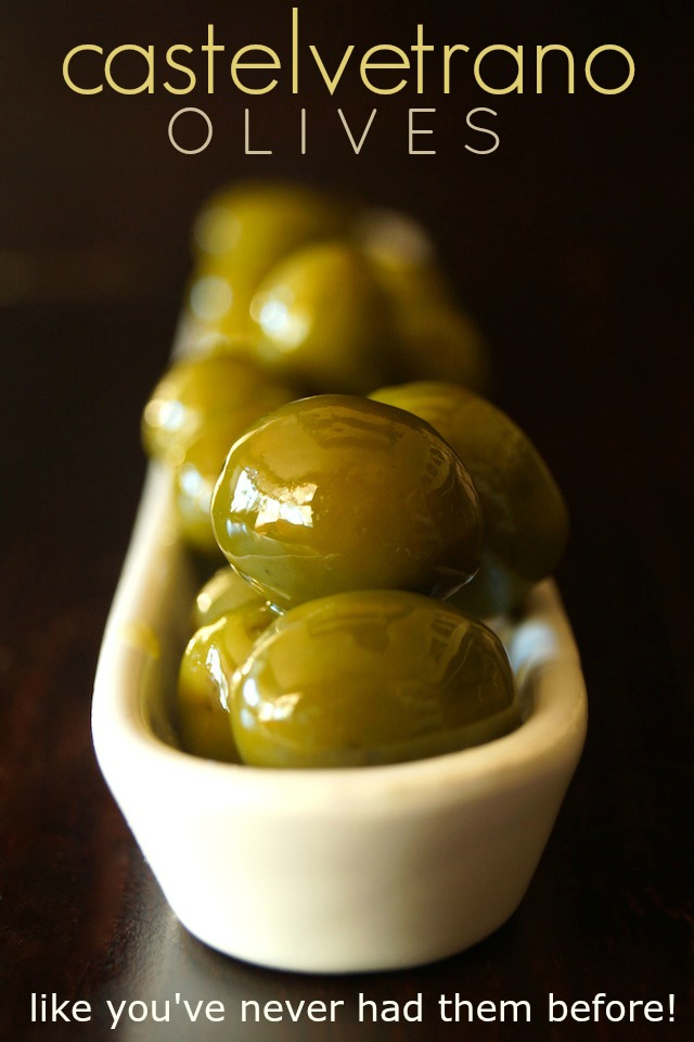 Warm Castelvetrano Olives in a long, narrow, white olive dish.