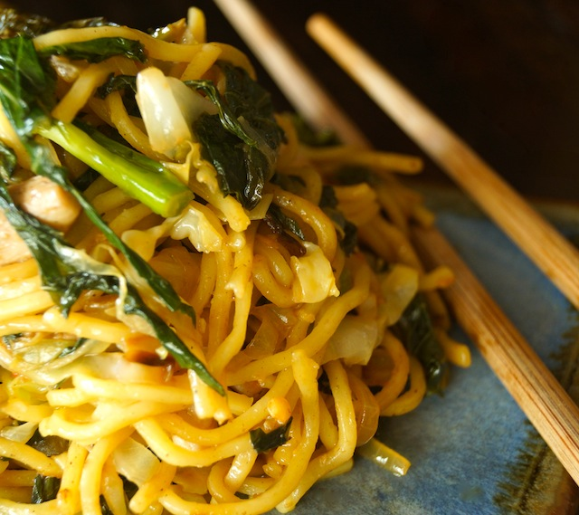 serving of Chinese Longevity Noodles with Gai Lan on ceramic plate with chopsticks