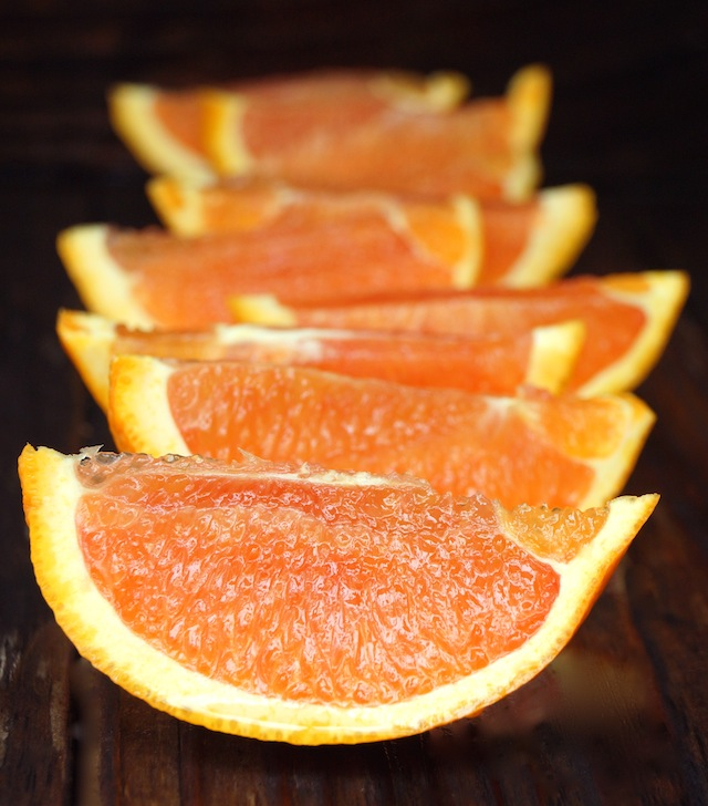 Several Cara Cara orange slices on a dark background.
