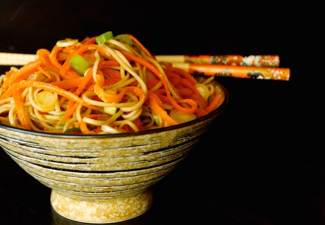 Ginger-Carrot Soba Noodles with chopsticks in a brown bowl.