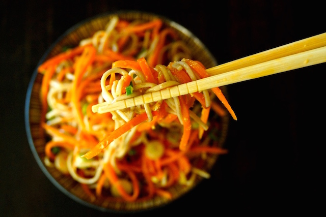 Ginger-Carrot Soba Noodles in a bowl with a bite being help in chopsticks above it.