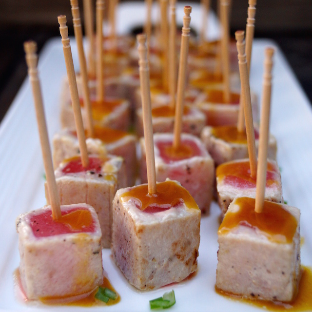 Wasabi Glazed Seared Ahi Tuna bites with toothpicks on white plate