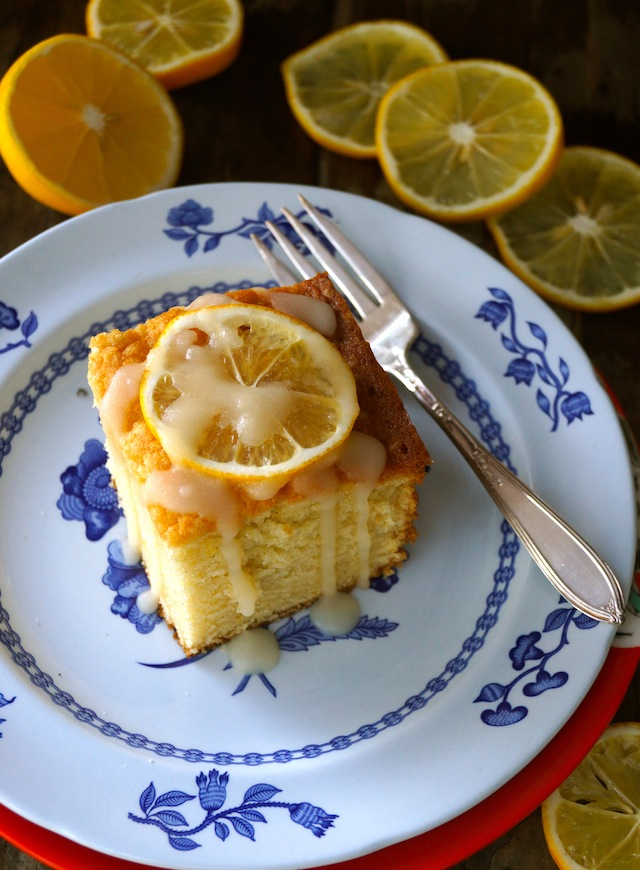 One slice of Lemon Hot Milk Cake on a white and blue plate with a silver fork, surrounded by fresh lemon slices.