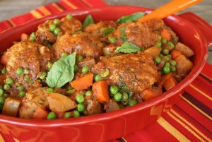 Stove-Top Spiced Turkey Meatball Stew - red casserole pan - striped red tablecloth - basil leaves | COOKINGONTHEWEEKENDS.COM