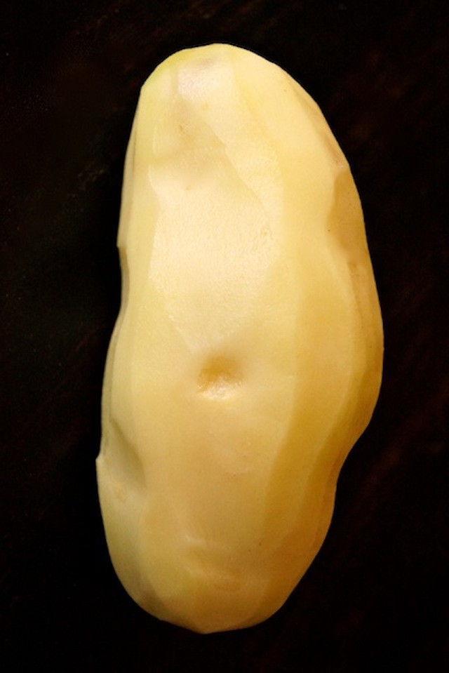 one large peeled russet potato with black background