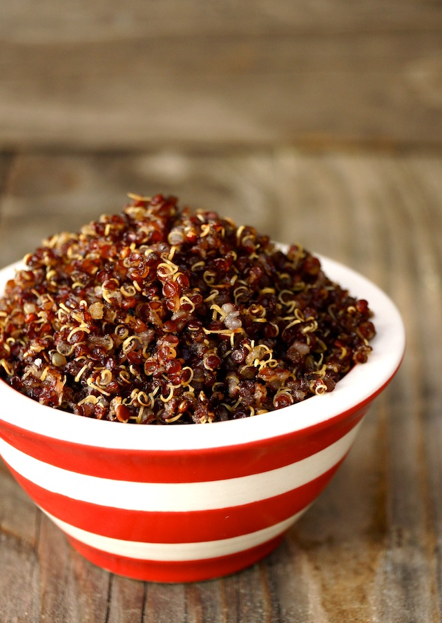 Red quinoa in a small red and white striped bowl.