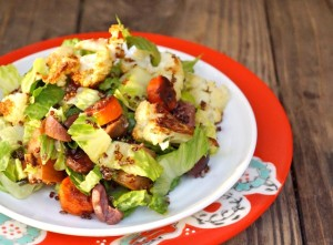 Roasted Vegetable Salad with Quinoa Crispson a small white plate that's on a red plate.