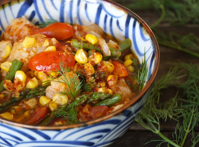 Summer Fish Stew in a blue and white bowl with fresh dill