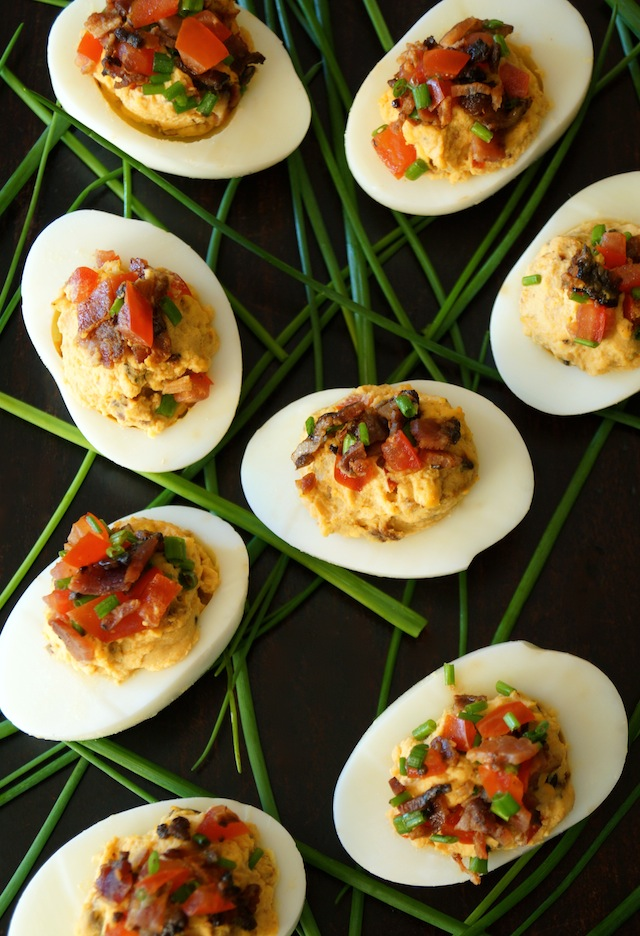 Chipotle-Bacon Deviled Eggs with fresh chives on black background