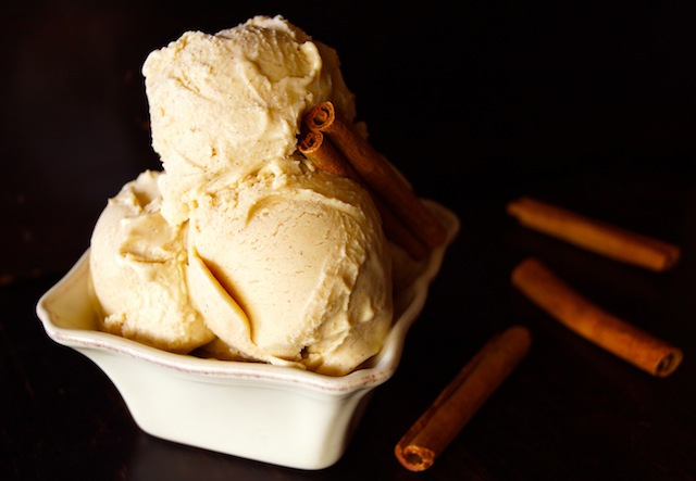 3 scoops of Cinnamon Ice Cream in square, cream-colored dish -- one cinnamon stick in the ice cream and three next to the dish.