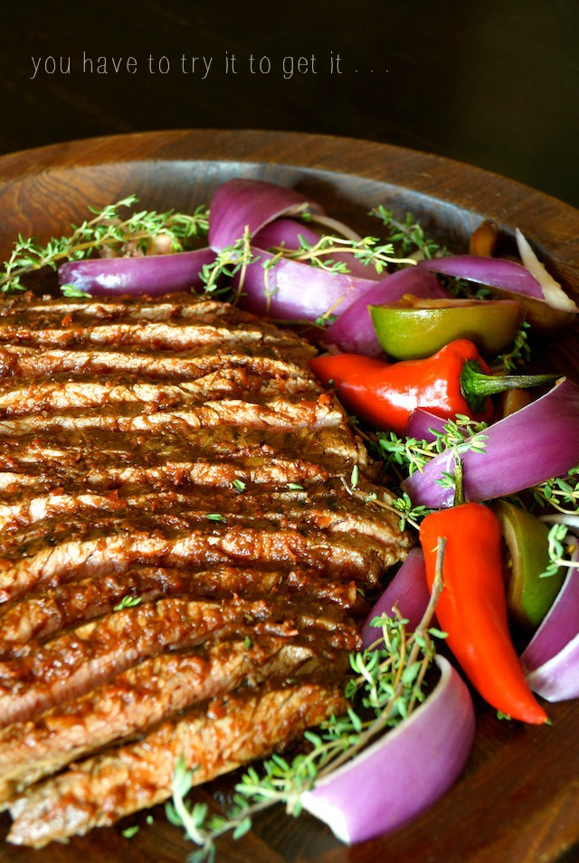 Red Goddess Flank Steak on a wooden platter with slices of purple onion, fresh thyme sprigs and 2 small red peppers