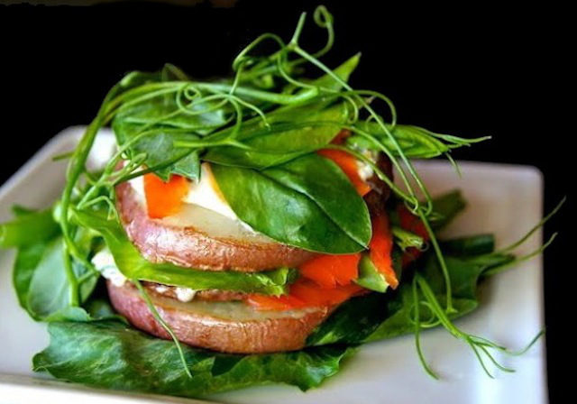 Stack of sliced red potatoes with smoked salmon and covered with snow pea shoots