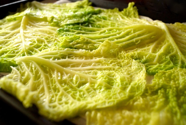 Savoy cabbage leaves spread out on sheet pan