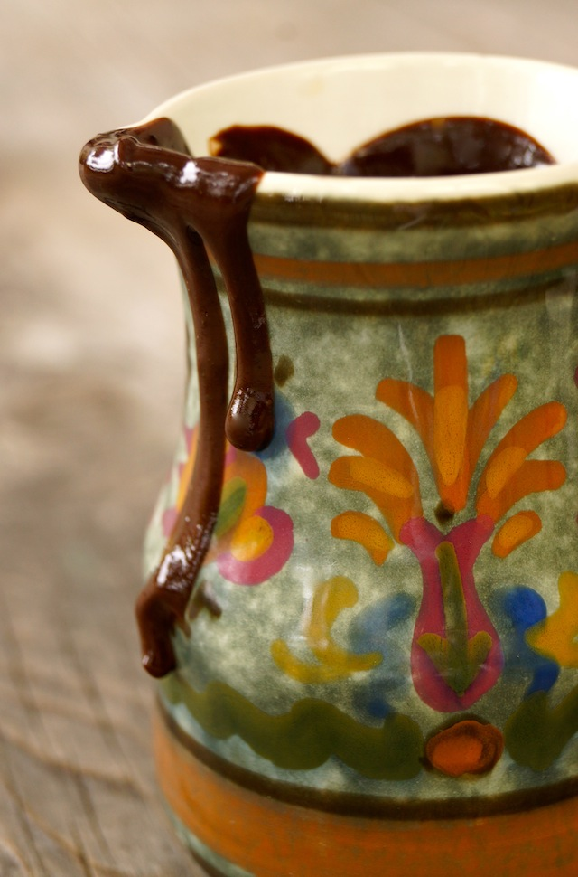 espresso chocolate sauce dripping from painted pretty green, oange , ceramic pitcher