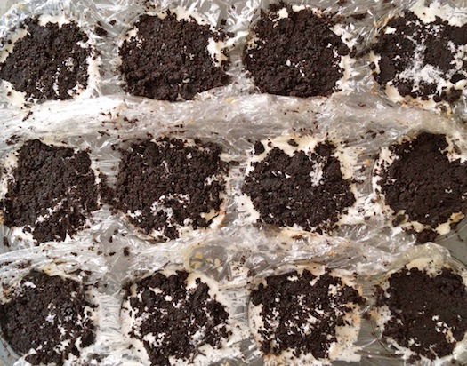 Individual mud pies with oreo crumbs on top in muffin tin
