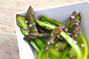 Peeled purple asparagus with green stems in a white square dish