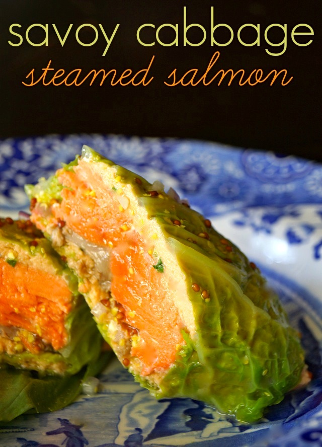 Cabbage Wrapped Salmon sliced in half on a blue plate.