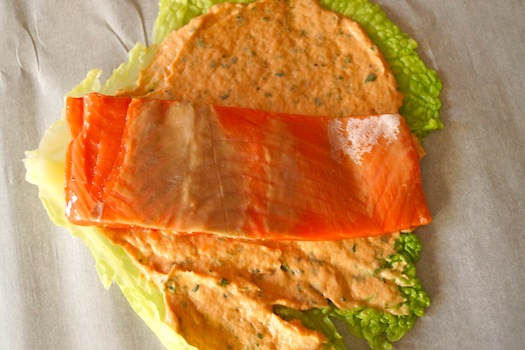 Prep for Cabbage Wrapped Salmon, with salmon fillet on top of cabbage leaf and salmon spread.