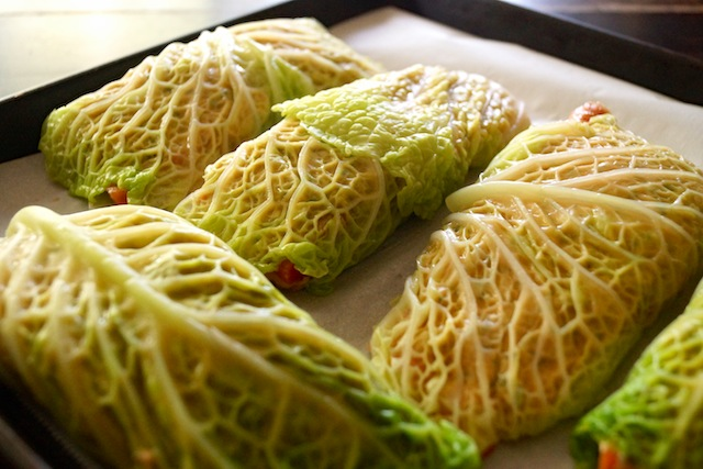 cabbage leaves wrapped abround salmon fillets on baking sheet.