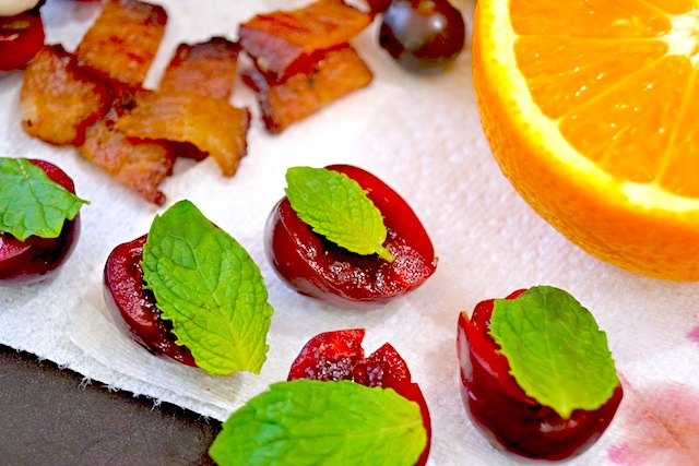 A few halved cherries with mint leaves on top of them on a paper towel.