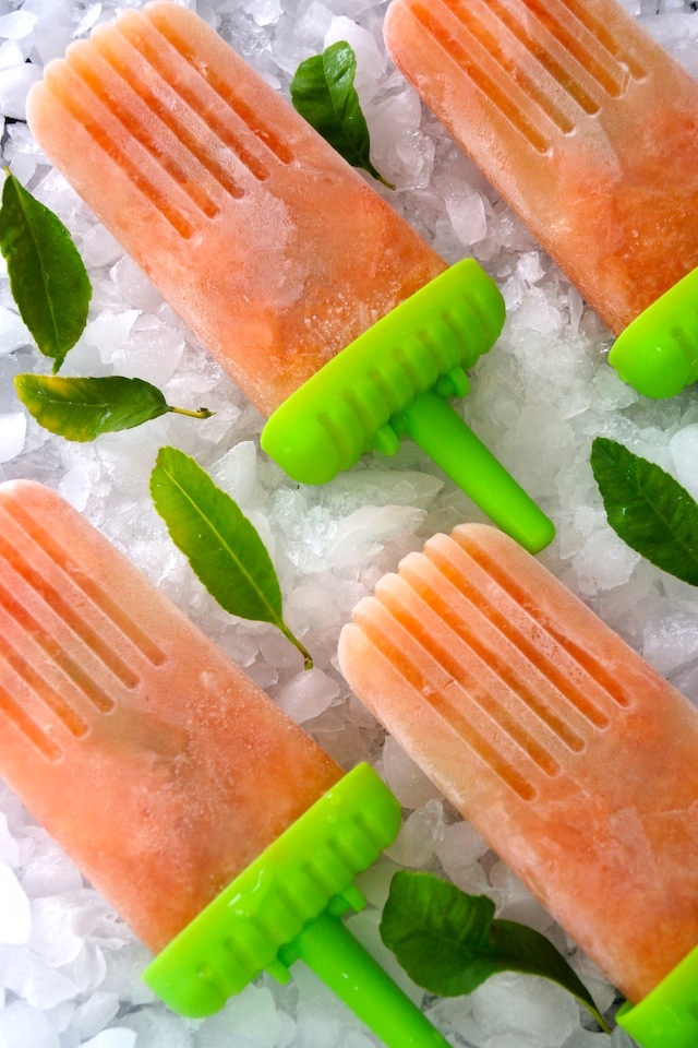 4 Honey Grapefruit Popsicles on ice with pretty green leaves.