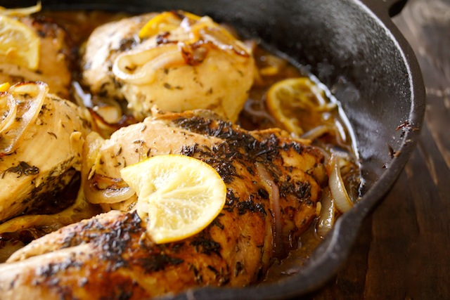 Skillet Braised Chicken Recipe with Caramelized Lemon-Shallot Sauce in cast iron pan with lemon slices.