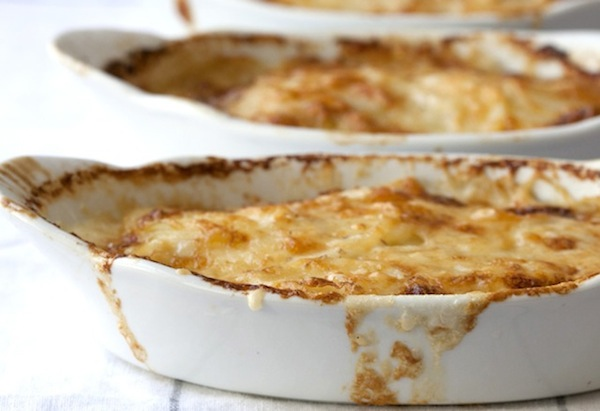 Potato Gratin with Green Chile spilling over white dish
