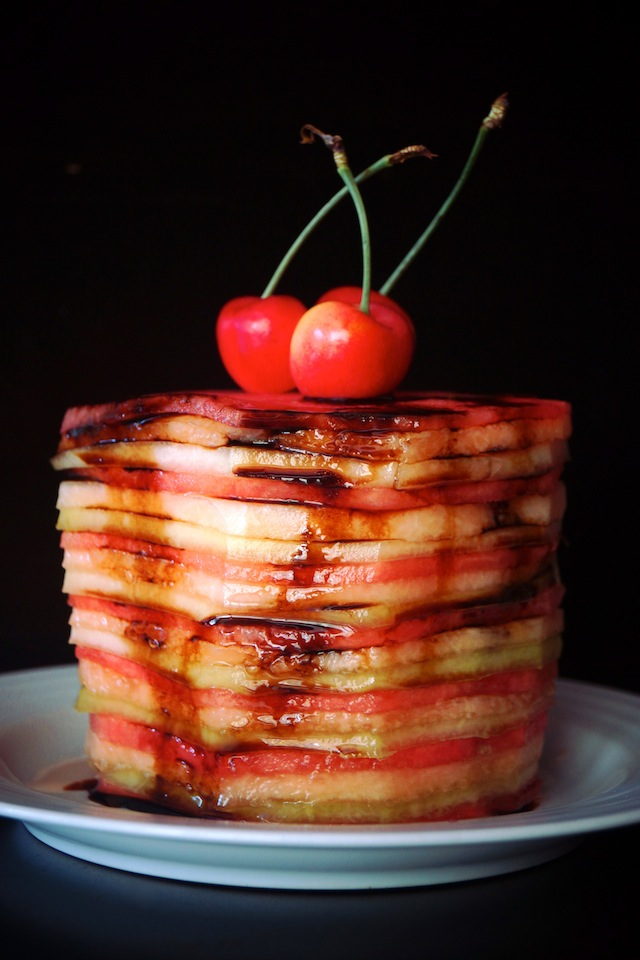 Balsamic Glazed Melon Cake pictured is a tall stack of super thinly sliced melons in a variety of colors with 3 cherries on top.